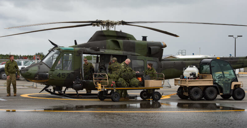 Canadian Armed Forces members unload a CH-147 helicopter.