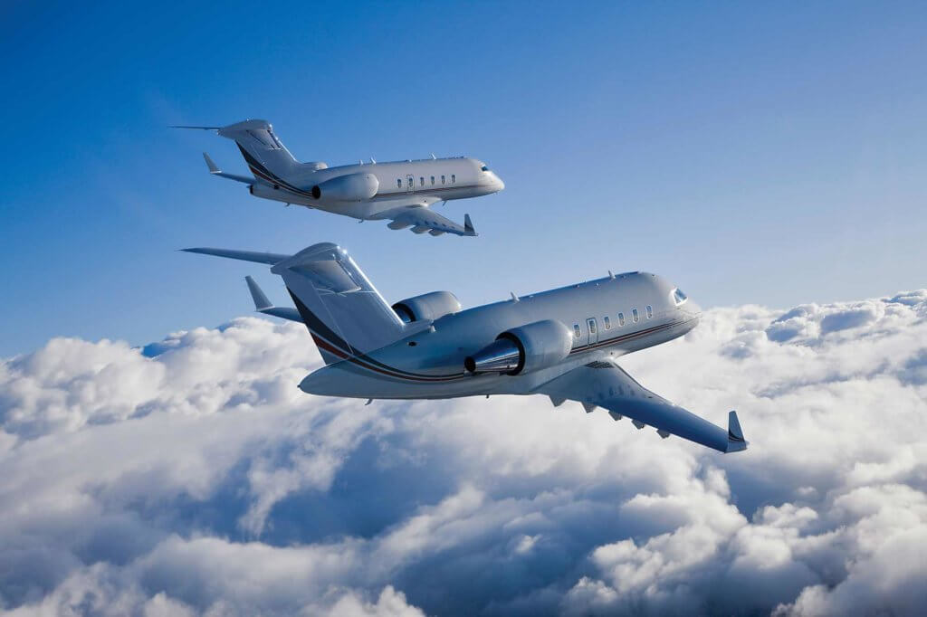 Two Bombardier Challenger business aircraft flying parallel.