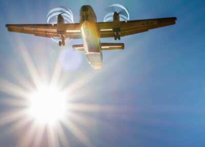 A plane flies overhead with the sun in the background.