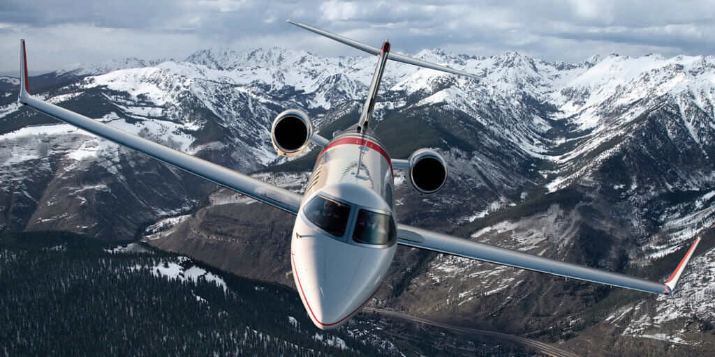 Flying Learjet aircraft in the cloudy sky