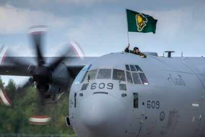 A man holds a London Knights flag while peeking out the top of a large Canadian Armed Forces plane