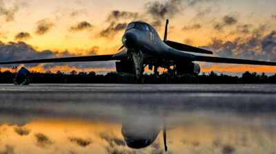 B-1B Bomber sitting on ground, with reflection in a puddle in the foreground.