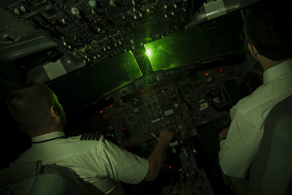 Two pilots sit in an airplane cockpit with a laser glaring through the windshield.