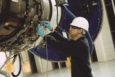 A Vector technician works on an aircraft engine..