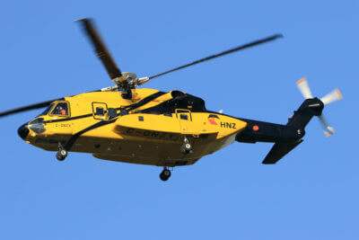 Yellow HNZ helicopter flies through the air.