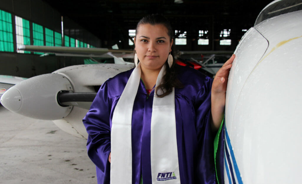Diana Wabano stands near two planes in a hangar.