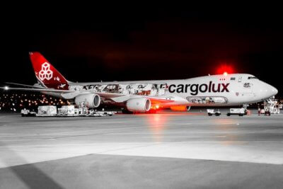 Cargolux aircraft rests on the ground at night, with red lights beaming toward the camera.