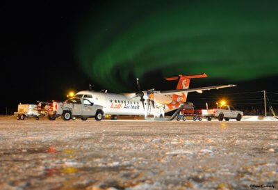 An Air Inuit Dash 8-300 rests on the ground with the Northern Lights flashing overhead