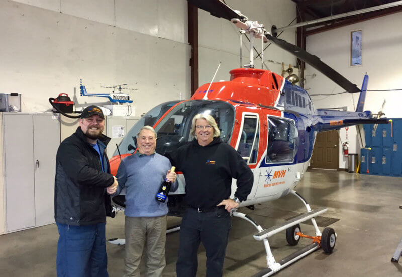 "Richard Alzetta (middle) ""semi-retired"" in 2011, but still instructs part-time, flying about 300 to 400 hours a year. Here, he celebrates his landmark with Paul Bergeron (right), Mountain View Helicopters president. Mountain View Helicopters Photos"