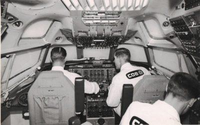 Black and white photo of three men in a CAE simulator