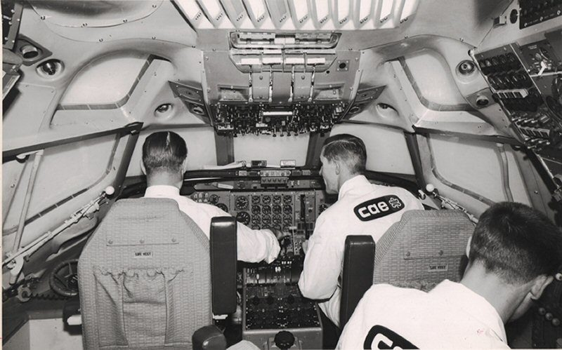 Black and white photo of three men in a CAE simulator