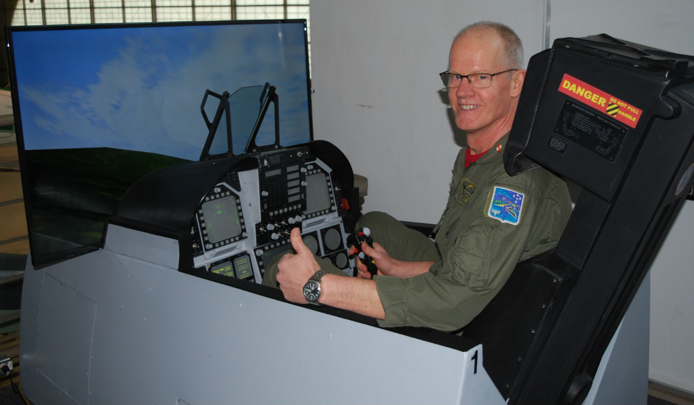 Air Combat Zone specializes in delivering an authentic fighter pilot experience through state-of-the-art simulation. Here, owner Steve Bigg climbs into the cockpit to demonstrate how to fly the F/A-18C Hornet simulators. Ben Forrest Photo