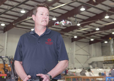A college instructor flies a small drone inside a facility in London, Ontario.