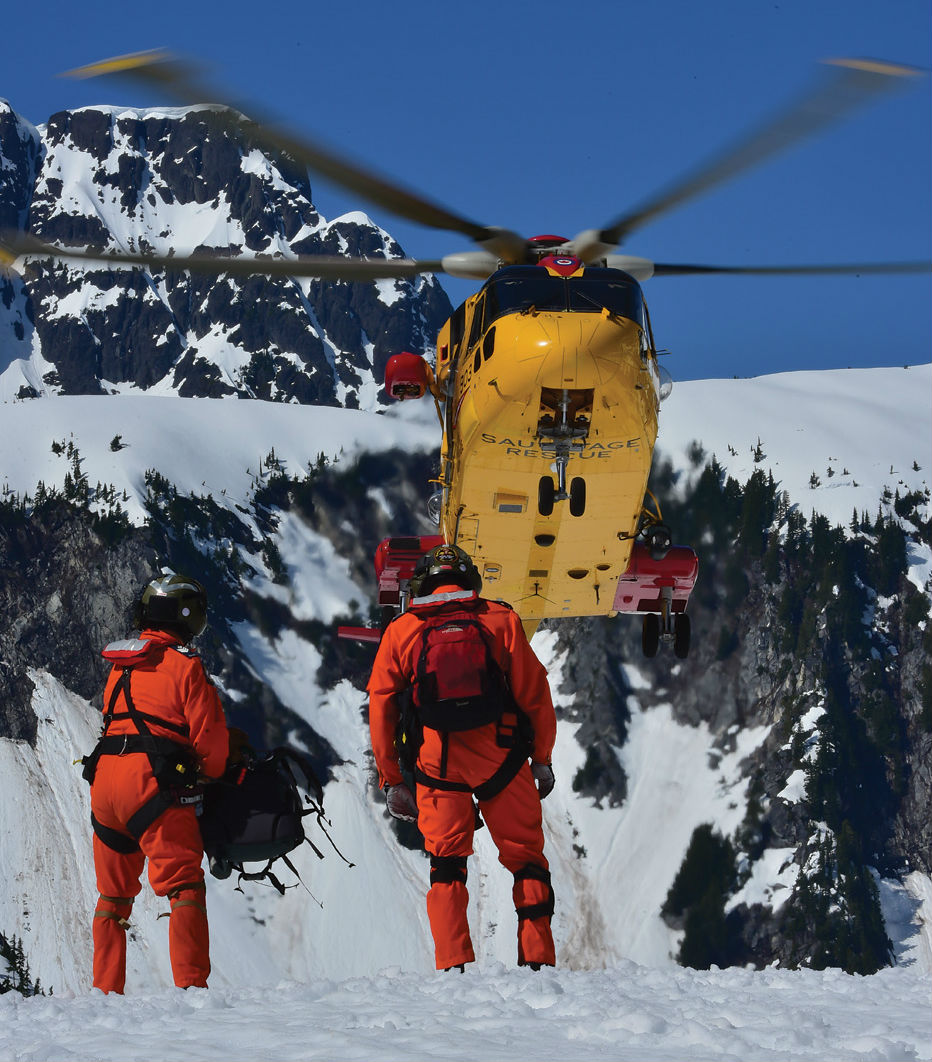 CH-149 Cormorant in front of snowy mountains, with two men standing on snowy ground in the foreground.