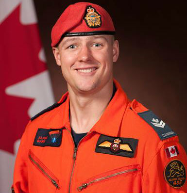 MCpl Alfred Barr in orange uniform, with Canadian flag in the background