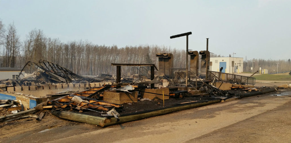 Ignited by blowing sparks, the airport lost its old administration building, a trade shop and, ironically, the fire hall--which went up when crews and vehicles were out protecting the fuel farm. YMM Photo