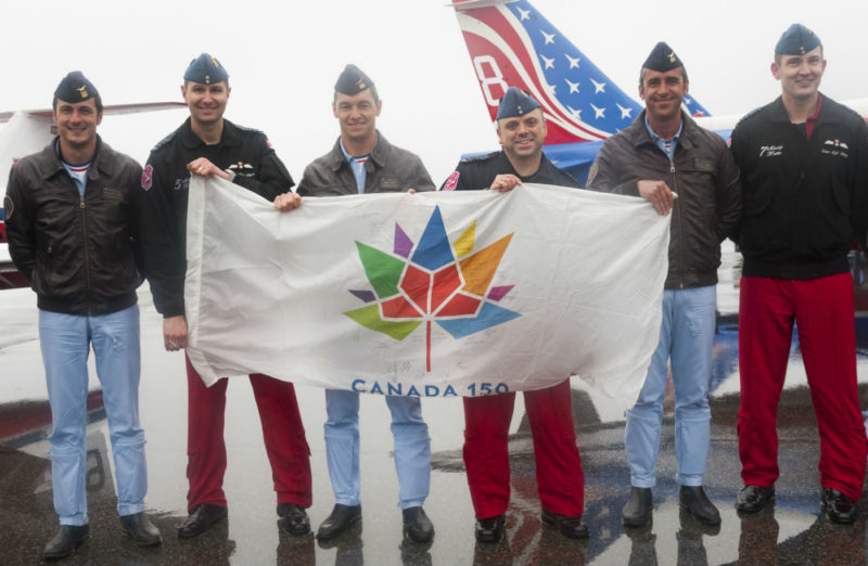 Members of the Canadian Forces Snowbirds and La Patrouille de France hold an autographed Canada 150 flag.