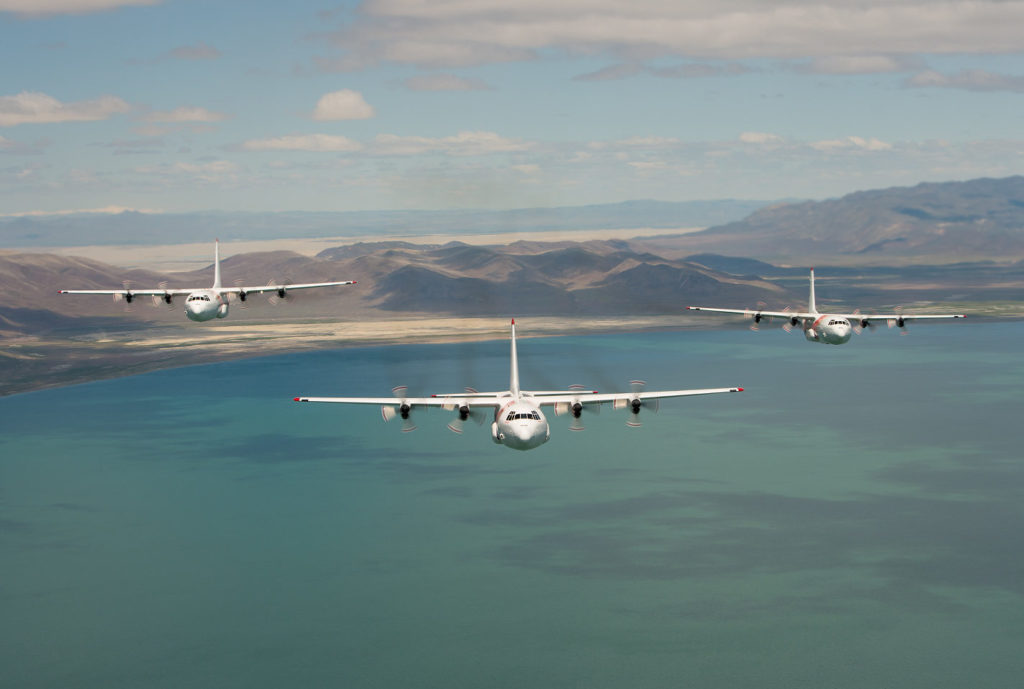 Three C-130 Hercules aircraft fly over a body of water, with mountains in the background.