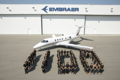 Embraer employees stand in front of the 1,100th business jet the company has delivered, a Phenom 300