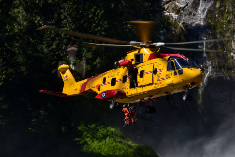 Two search and rescue workers hang from a line connected to a Cormorant helicopter