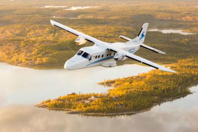 a Summit Air Dornier 228 overflies an idyllic rural scene.