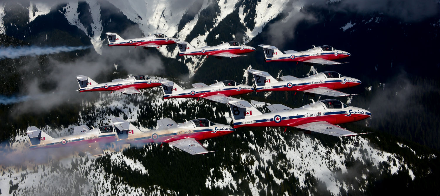 The Snowbirds fly in formation with mountains in the background