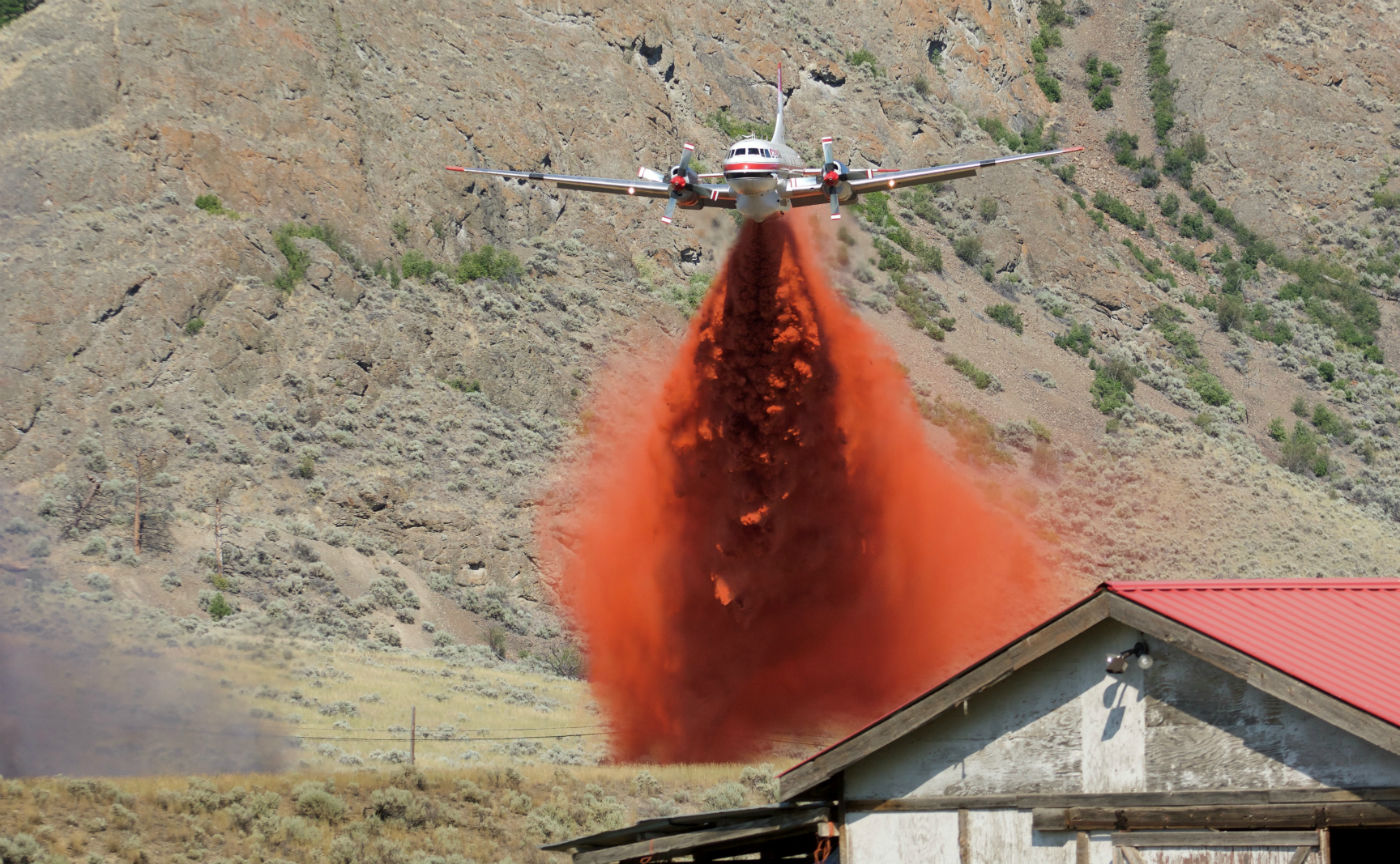 A Convair CV580 air tanker from Conair Aerial Firefighting dumps flame retardant. Susanne De Montreuil Photo