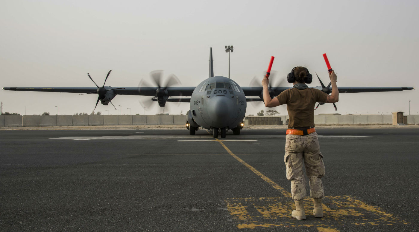 A technician guides a CC-130J Hercules as it returns from its first mission with Operation IMPACT in Kuwait, Iraq, on July 12, 2017. Op IMPACT Imaging