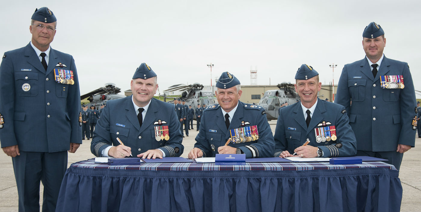Col Peter Allan, outgoing 12 Wing commanding officer (seated, left); MGen Christian Drouin, Commander of 1 Canadian Air Division; and Col Sid Connor sign the official documents allowing Col Connor to take command of the wing, while CWO Jacques Boucher, 1 Canadian Air Division CWO (standing, left), and 12 Wing CWO David Hepditch (standing, right) observe during the Change of Command Parade at 12 Wing Shearwater, N.S., on July 19, 2017. Cpl Jennifer Chiasson Photo