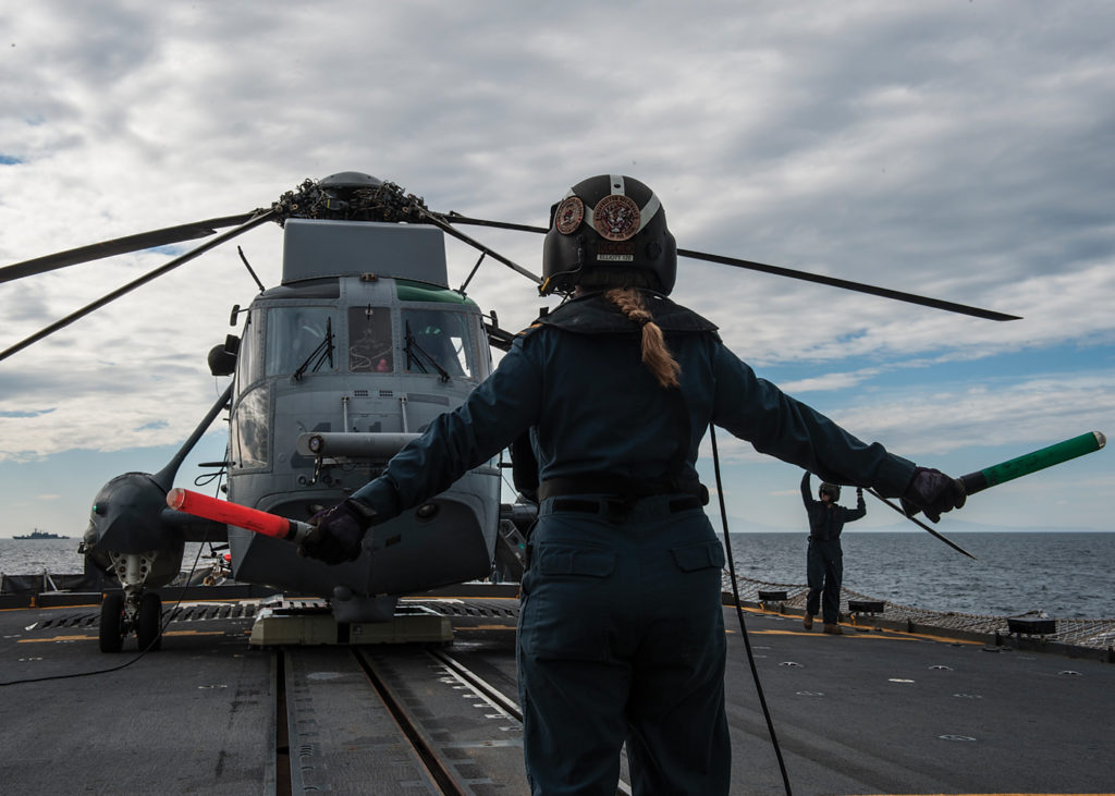 HMCS Fredericton's air detachment deck director signals the deck crew during the start-up of an embarked CH-124 Sea King helicopter. DND Photo