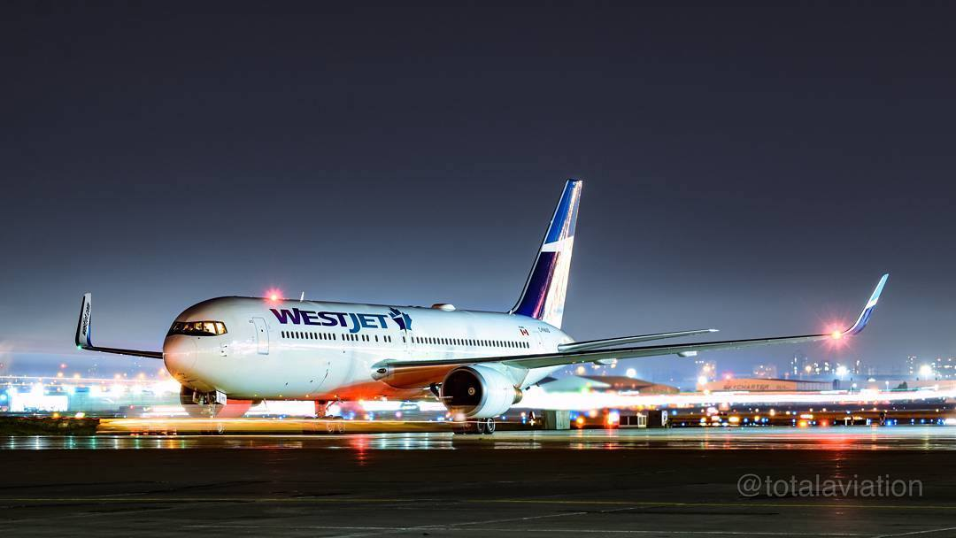 A WestJet Boeing 767 rests on the tarmac at night. Photo submitted by Instagram user @totalaviation using #skiesmag