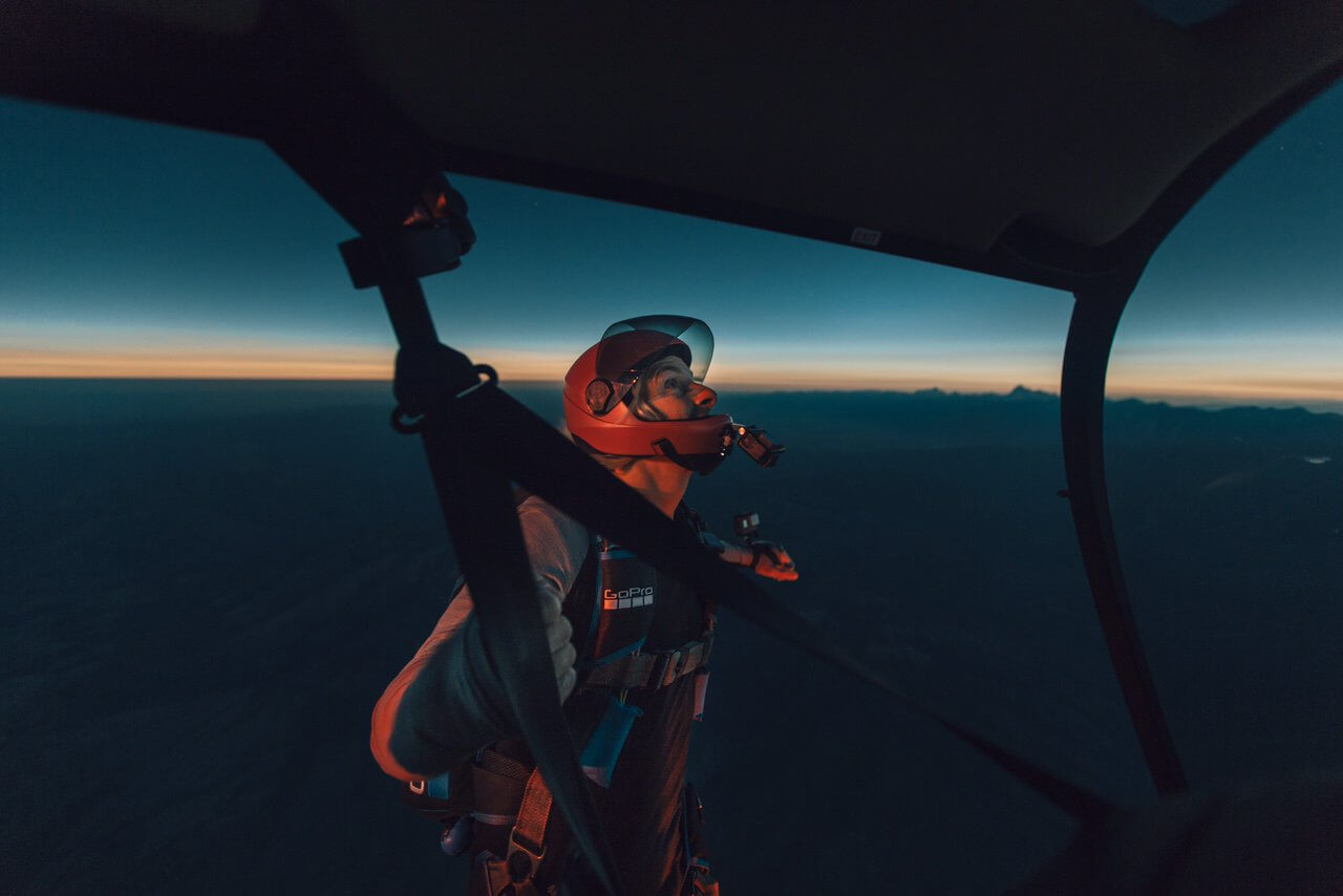 "GoPro athlete Chris Farro watches the total solar eclipse from the skids of York Galland's Robinson R66, ""moments before jumping into the eeriest sky I have ever seen."" Abe Kislevitz Photo/Instagram: @abekislevitz"