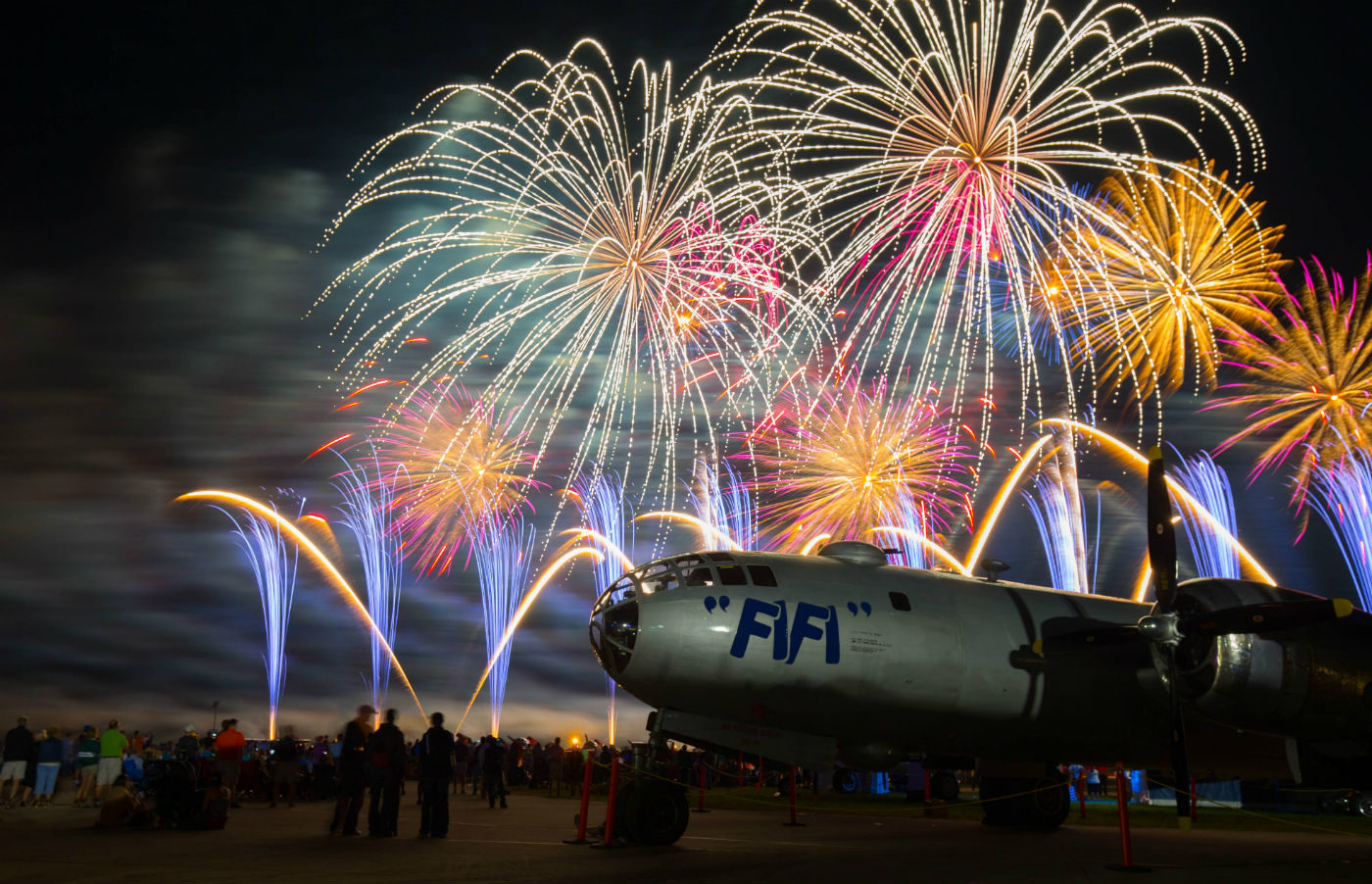 A newly restored Boeing B-29 sits on the tarmac during a beautiful firework display. Warren Liebmann Photo