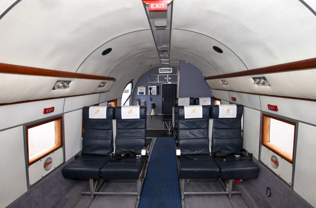 The DC-3's bright and airy cabin is adorned with wooden trim and window framing, and equipped with 14 passenger seats for the World Tour, eight forward and six aft. It is normally equipped with 30.