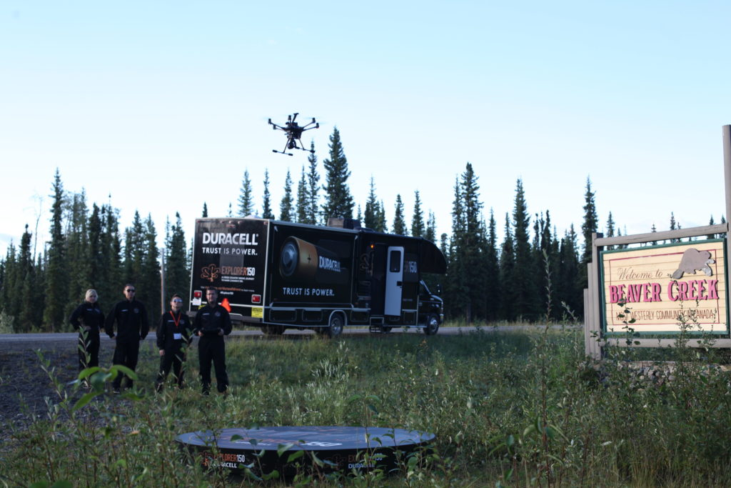 Three men stand in foreground as drone flies overhead
