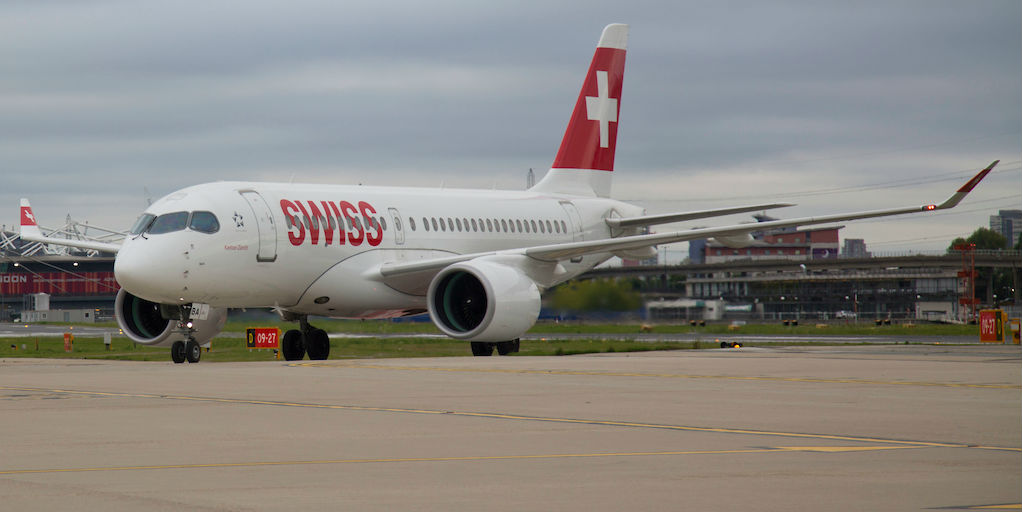Bombardier CS100 in SWISS livery rests on a runway.