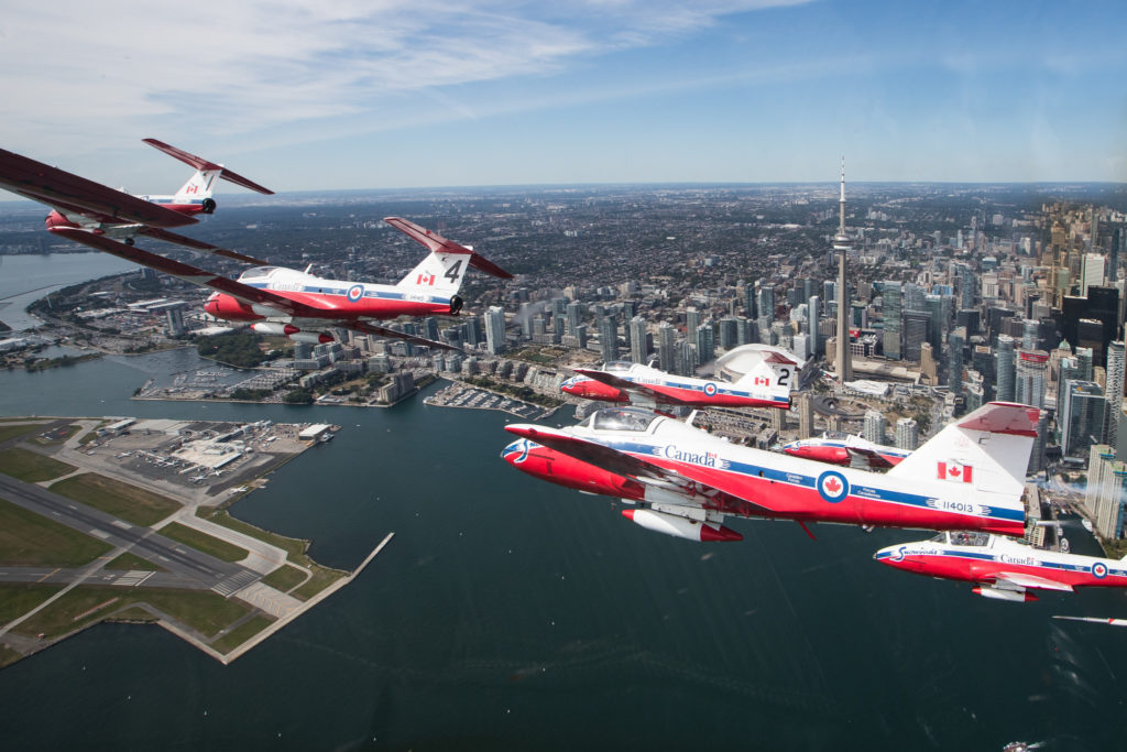 Snowbirds fly over Lake Ontario, with Toronto cityscape in background.