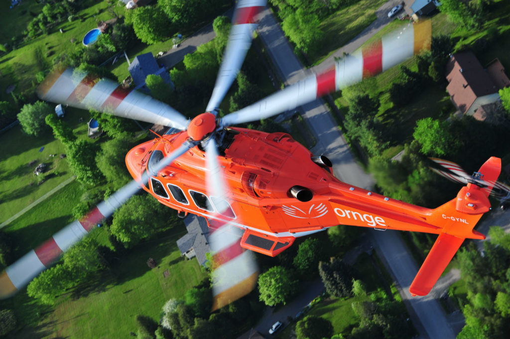 An Ornge Leonardo AW139 helicopter soars over the countryside.