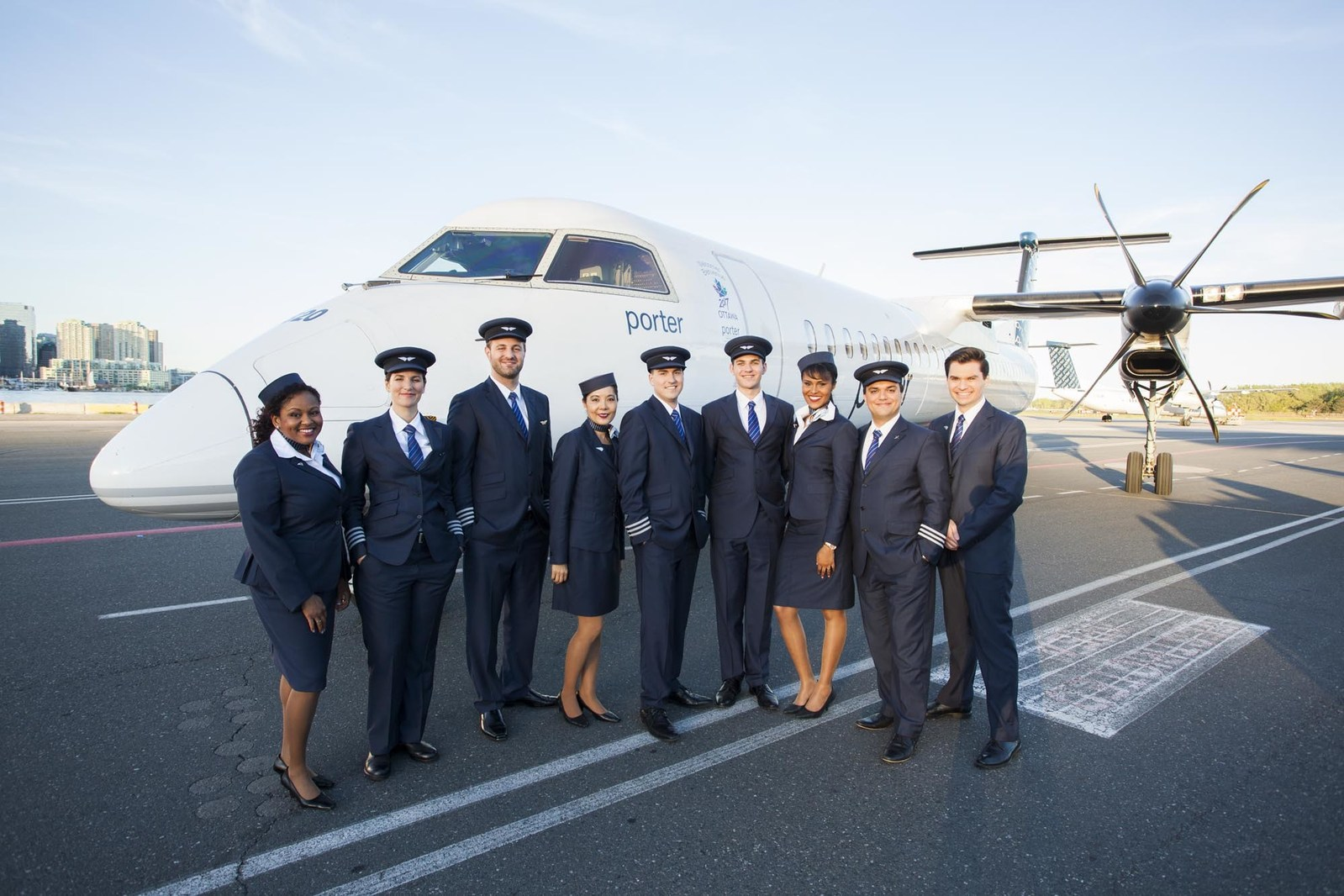Pilots and flight attendants stand next to Porter Q400 plane.
