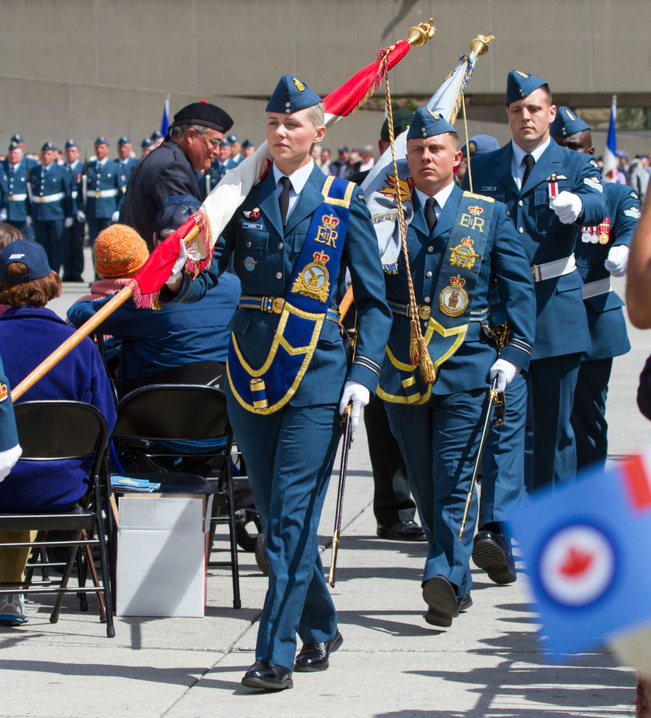 RCAF personnel march, holding colours.