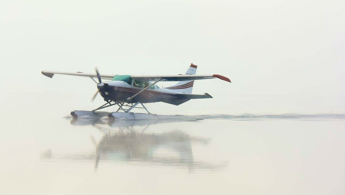 Amber Airways Cessna taxis through the morning fog on Schwatka Lake, Yukon.