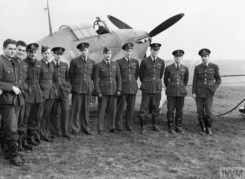 A group of pilots from the RCAF's No. 1 Squadron gather around one of their Hawker Hurricane Mk 1s at Prestwick, Scotland, on Oct. 30, 1940.