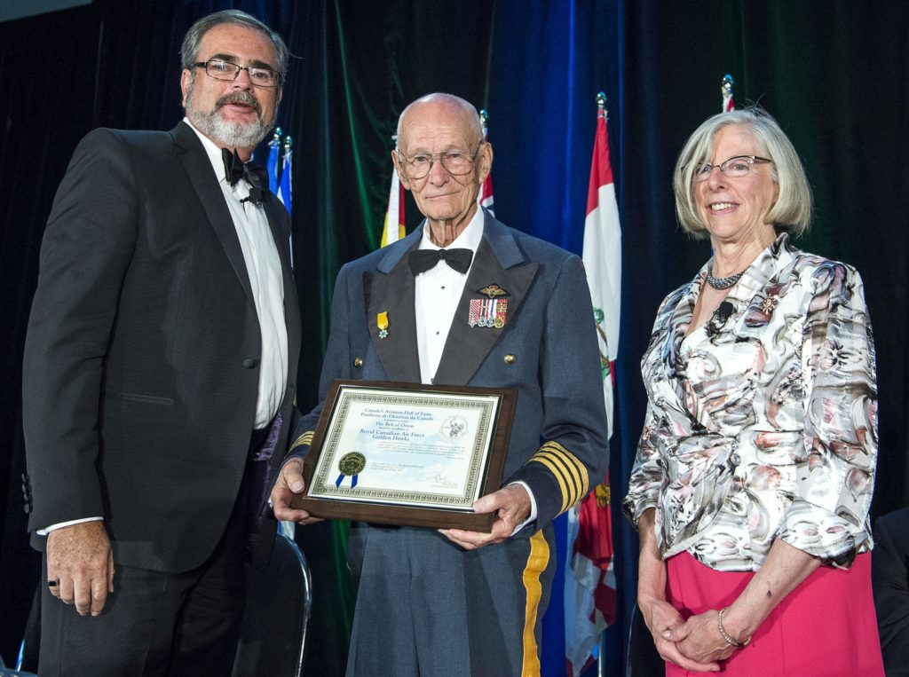 At the 2017 induction ceremonies for Canada's Aviation Hall of Fame, Fern Villeneuve, centre, is seen with the certificate for the Belt of Orion Award of Excellence presented to the Golden Hawks. At left is Hall board chairman, Rod Sheridan, with guest speaker and presenter Judith Guichon, the Lieutenant Governor of British Columbia. Rick Radell Photo