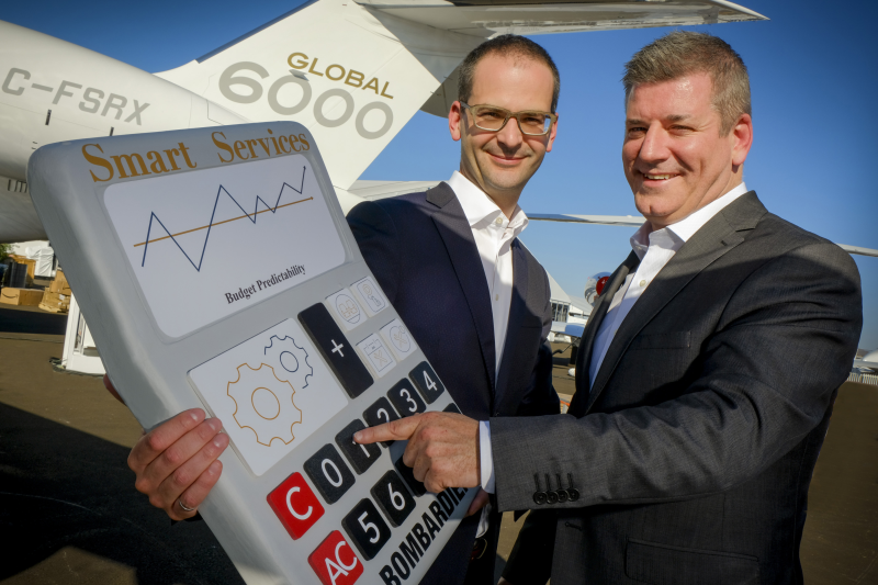 Two man stand next to aircraft, with giant calculator.