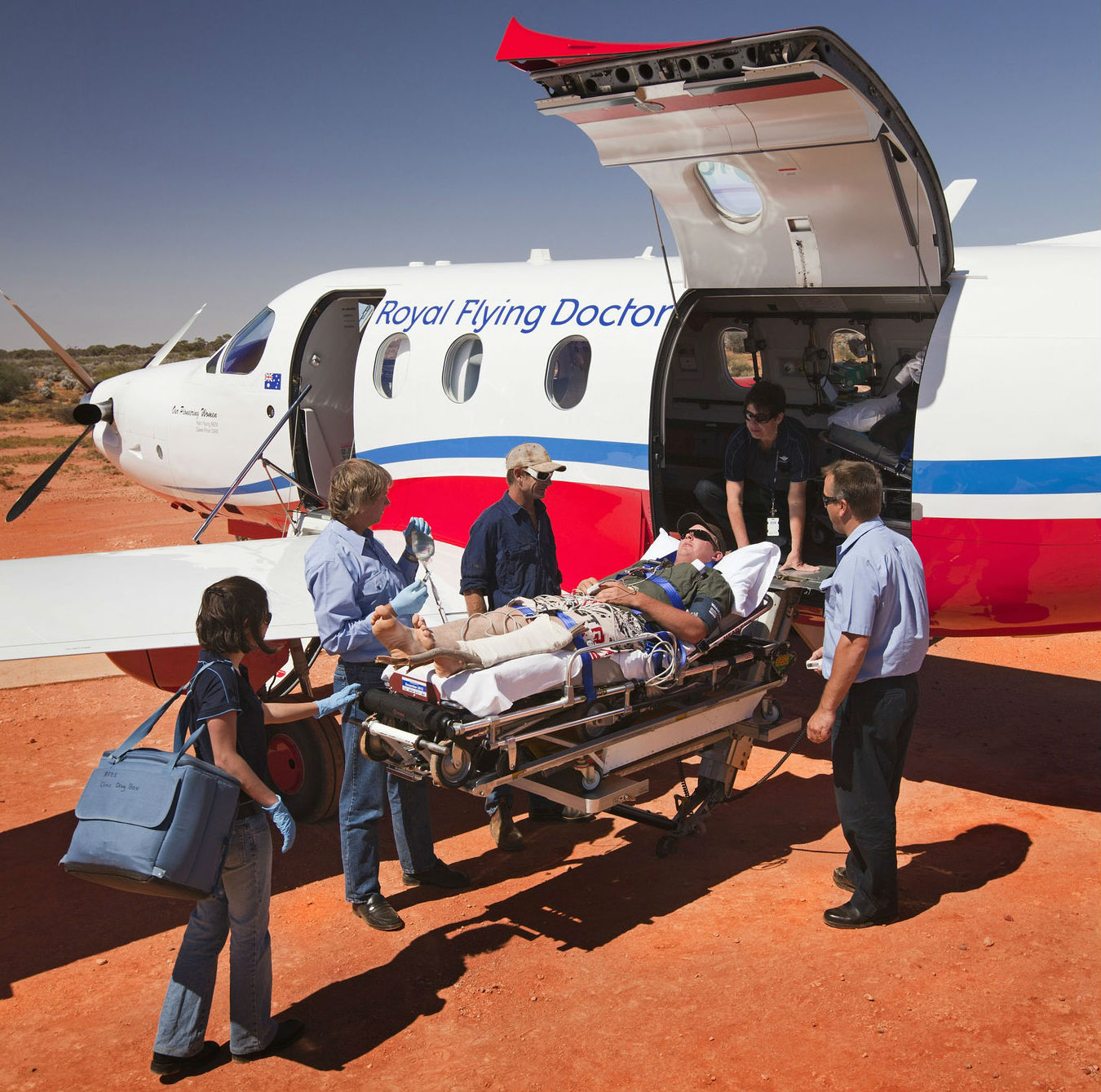 Royal Flying Doctor Service personnel load a patient into an aircraft.
