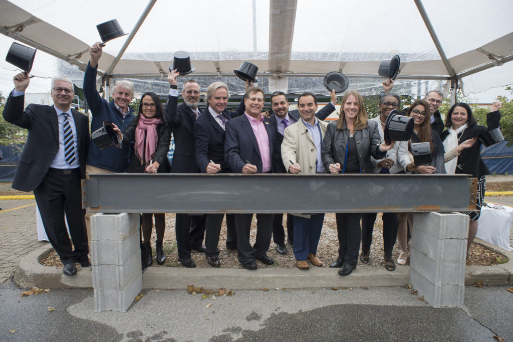 Administrators and partners of Centennial College hoist their top hats to celebrate the construction of the new 138,000 square-foot Centre for Aerospace and Aviation at Downsview Park.