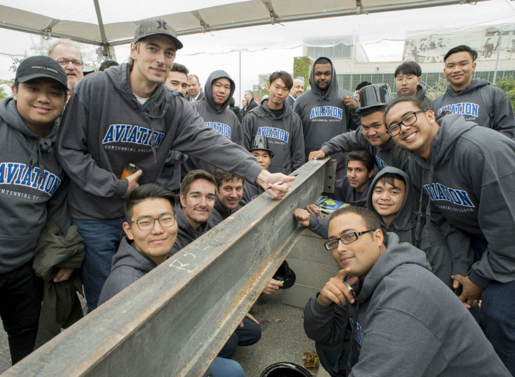 Centennial College aviation technician students sign the steel beam that will form part of the hangar under construction