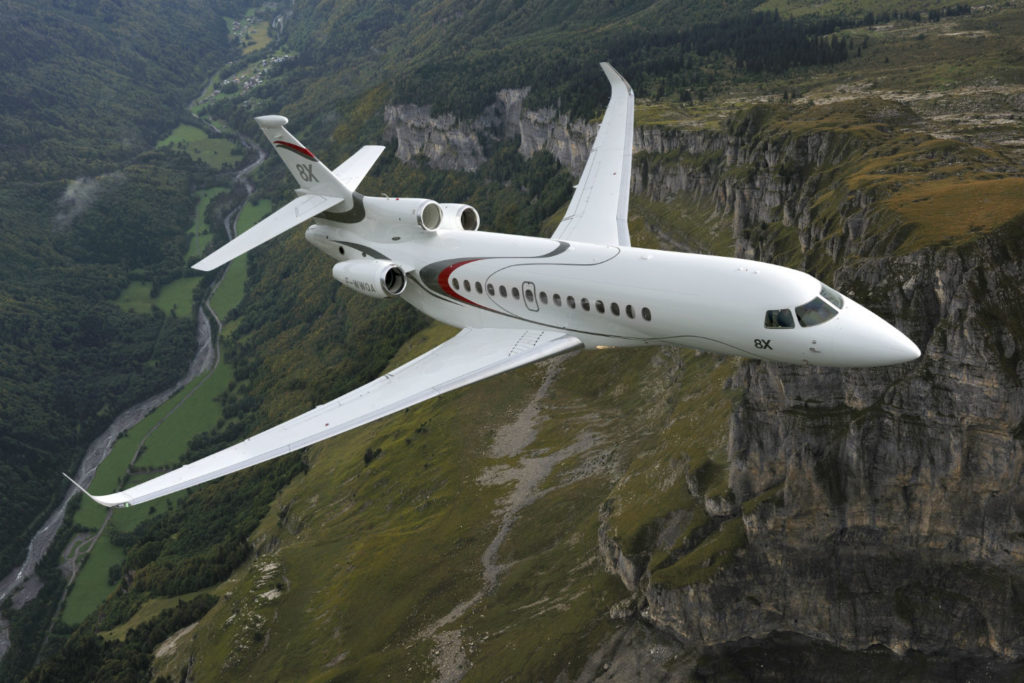 A Dassault Falcon 8X aircraft flies over picturesque terrain.