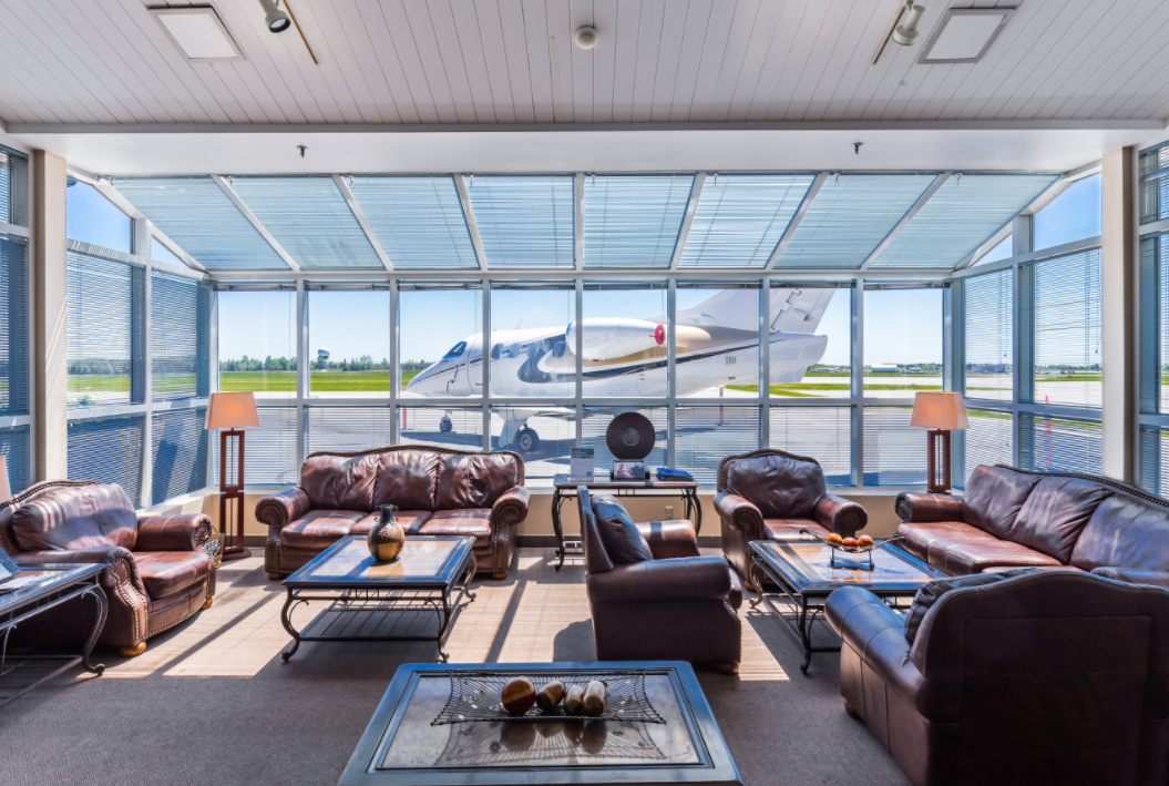 Inside a lounge at Ottawa MacDonald Cartier International Airport, looking out onto a small aircraft on the tarmac.