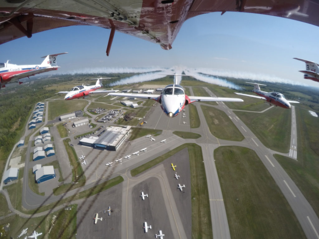The Canadian Forces Snowbirds fly over Peterborough Airport in the summer of 2016. This photo clearly shows the airport's development and facilities. DND Photo